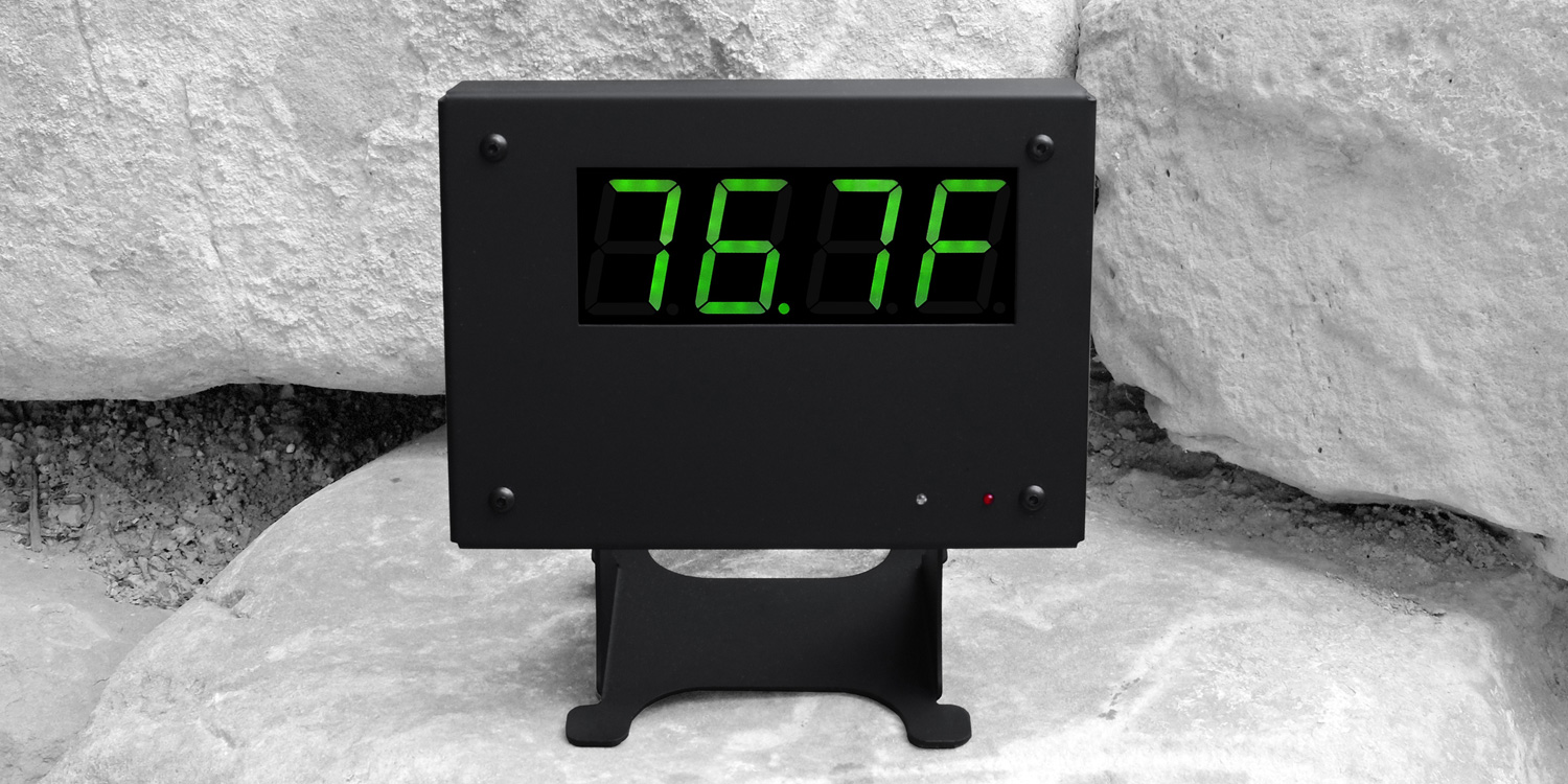 Black thermometer with stand on rocks